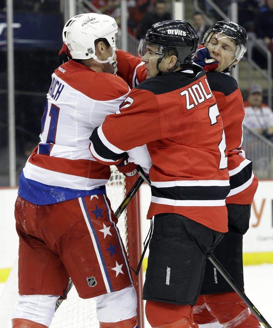 New Jersey Devils defenseman Marek Zidlicky, center, of the Czech Republic, breaks up a scuffle between Washington Capitals center Brooks Laich, left, and Travis Zajac during the first period of an NHL hockey game, Friday, Jan. 24, 2014, in Newark, N.J. (AP Photo/Julio Cortez)