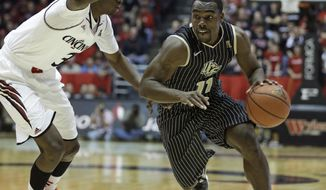 Central Florida guard Calvin Newell (11) drives past Cincinnati forward Shaquille Thomas in the second half of an NCAA college basketball game, Thursday, Jan. 23, 2014, in Cincinnati. Newell led UCF with 12 points in the game won by Cincinnati 69-51. (AP Photo/Al Behrman)