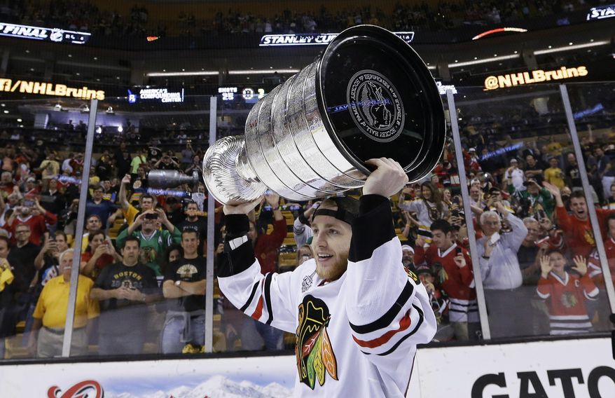 """FILE - In this June 24, 2013, file photo, Chicago Blackhawks right wing Patrick Kane hoists the Stanley Cup after the Blackhawks beat the Boston Bruins 3-2 in Game 6 of the NHL hockey Stanley Cup Finals in Boston. Kane's maturation as a person and player seems to have helped the Chicago Blackhawks win two of the last four Stanley Cups, and improves the Americans' chances to win Olympic gold in hockey since the """"Miracle on Ice,"""" in 1980. (AP Photo/Elise Amendola, File)"""