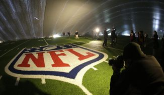 FILE - In this Jan. 15, 2014 file photo, the NFL logo at midfield of MetLife Stadium is illuminated by lights on television reporters' videocameras as members of the media are given a tour under a tarp used by crews to keep the turf dry ahead of Super Bowl XLVIII in East Rutherford, N.J. As the Denver Broncos and Seattle Seahawks prep for their Feb. 2, 2014 showdown in the Super Bowl, a legal fight is playing out over the very turf installed months ago at the NFL title game's venue. Taylor Turf Installation Inc. is suing the MetLife Stadium's operators and the company that hired the suburban St. Louis company, seeking more than $292,000 that Taylor Turf claims it still is owed for hustling to install the  stadium's playing surface last summer. (AP Photo/Julio Cortez, File)