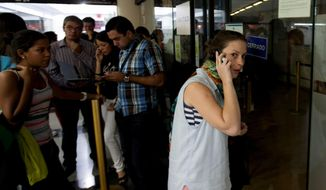 A woman speaks on her cell as she seeks information about flight sales from a closed United Airlines office in Caracas, Venezuela, Friday, Jan. 24, 2014.  Delta, American Airlines and Panama's Copa Airlines were also among carriers whose offices were either closed or had halted sales on Friday after the government devalued the local currency for flights abroad. (AP Photo/Alejandro Cegarra)