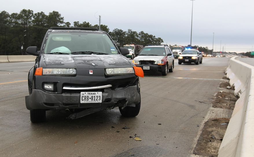 Steady rain Thursday led to icy road conditions as temperatures dropped Friday morning, Jan. 24, 2014 causing several accidents as motorists made their morning commute on I-45,  in Conroe, Texas. (AP Photo/ The Courier, Jason Fochtman)