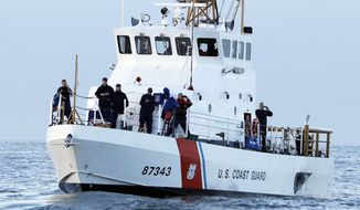 **FILE** Crewmen on a U.S. Coast Guard vessel watch the first heat of the first round of the Mavericks Invitational big wave surf contest Friday, Jan. 24, 2014, in Half Moon Bay, Calif. (AP Photo/Eric Risberg)