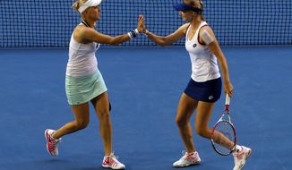 Russia's Ekaterina Makarova, right, and  Elena Vesnina celebrate a point  won over  Italy's Sara Errani and Roberta Vinci during their women's doubles final at the Australian Open tennis championship in Melbourne, Australia, Friday, Jan. 24, 2014.(AP Photo/Eugene Hoshiko)
