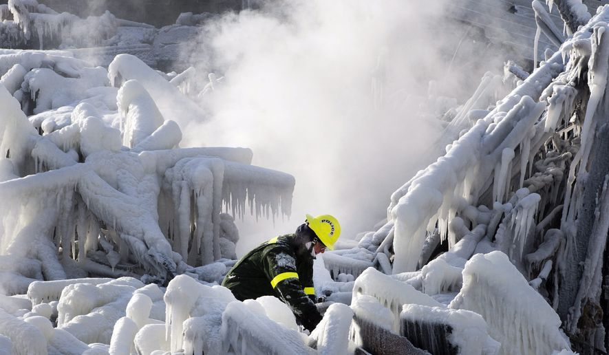 Rescue personnel search through icy rubble to try to locate more victims of a fire that destroyed a seniors' residence Friday, Jan. 24, 2014, in L'Isle-Verte, Quebec. Five people are confirmed dead and 30 people are still missing, while with cause of Thursday morning's blaze is unclear police said. Authorities are using steam to melt the ice and to preserve any bodies that are buried. (AP Photo/The Canadian Press, Ryan Remiorz)