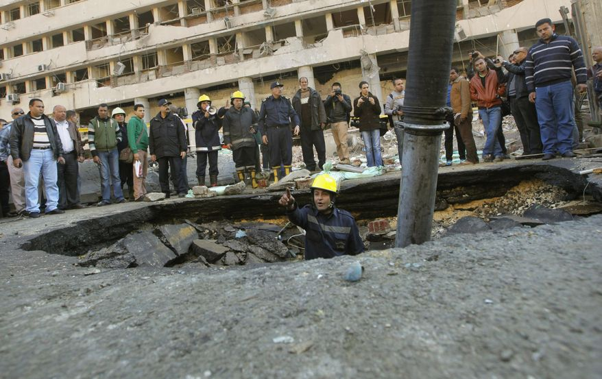 An Egyptian firefighter checks a crater made by a blast at the Egyptian police headquarters in downtown Cairo, Egypt, Friday, Jan. 24, 2014. Three bombings hit high-profile areas around Cairo on Friday, including a suicide car bomber who struck the city's police headquarters, killing several people in the first major attack on the Egyptian capital as insurgents step up a campaign of violence following the ouster of the Islamist president. (AP Photo/Amr Nabil)