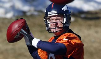 An extra football crosses in front of Denver Broncos quarterback Peyton Manning as he throws another during NFL football practice at the team's training facility in Englewood, Colo., on Friday, Jan. 24, 2014. The Broncos are scheduled to play the Seattle Seahawks in Super Bowl XLVIII on Feb. 2. (AP Photo/Ed Andrieski)