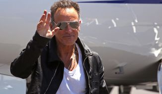 American performer Bruce Springsteen, waves as he arrives at the airport in Cape Town, South Africa, Friday, Jan. 24, 2014. Bruce Springsteen will begin his first South African tour on Sunday, Jan. 26, in Cape Town. (AP Photo/Schalk van Zuydam)