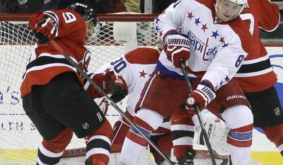 Washington Capitals defenseman Dmitry Orlov, right, of Russia, takes the puck away from New Jersey Devils forward Joe Whitney, left, during Whitney's NHL debut in the first period of an NHL hockey game, Friday, Jan. 24, 2014, in Newark, N.J. (AP Photo/Julio Cortez)
