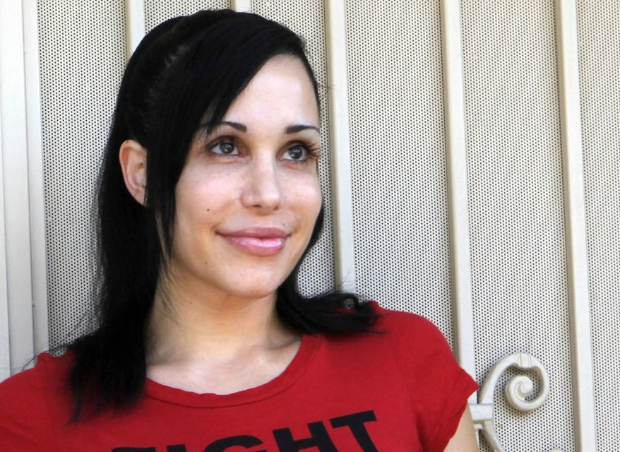 FILE - In this May 19, 2010 this file photo, Nadya Suleman stands  outside her home in La Habra, Calif. Los Angeles County prosecutors  said Monday, Jan. 13, 2014, they have charged  Suleman with welfare fraud. The district attorney's office said on Monday that Suleman failed to report nearly $30,000 in earnings while applying for public assistance last year. Suleman gained fame when she gave birth to octuplets in 2009. (AP Photo/Damian Dovarganes, File)