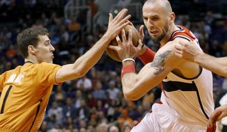 Washington Wizards' Marcin Gortat, right, of Poland, gets the balled stripped by Phoenix Suns' Goran Dragic (1), of Slovenia, during the first half of an NBA basketball game, Friday, Jan. 24, 2014, in Phoenix. (AP Photo/Ross D. Franklin)