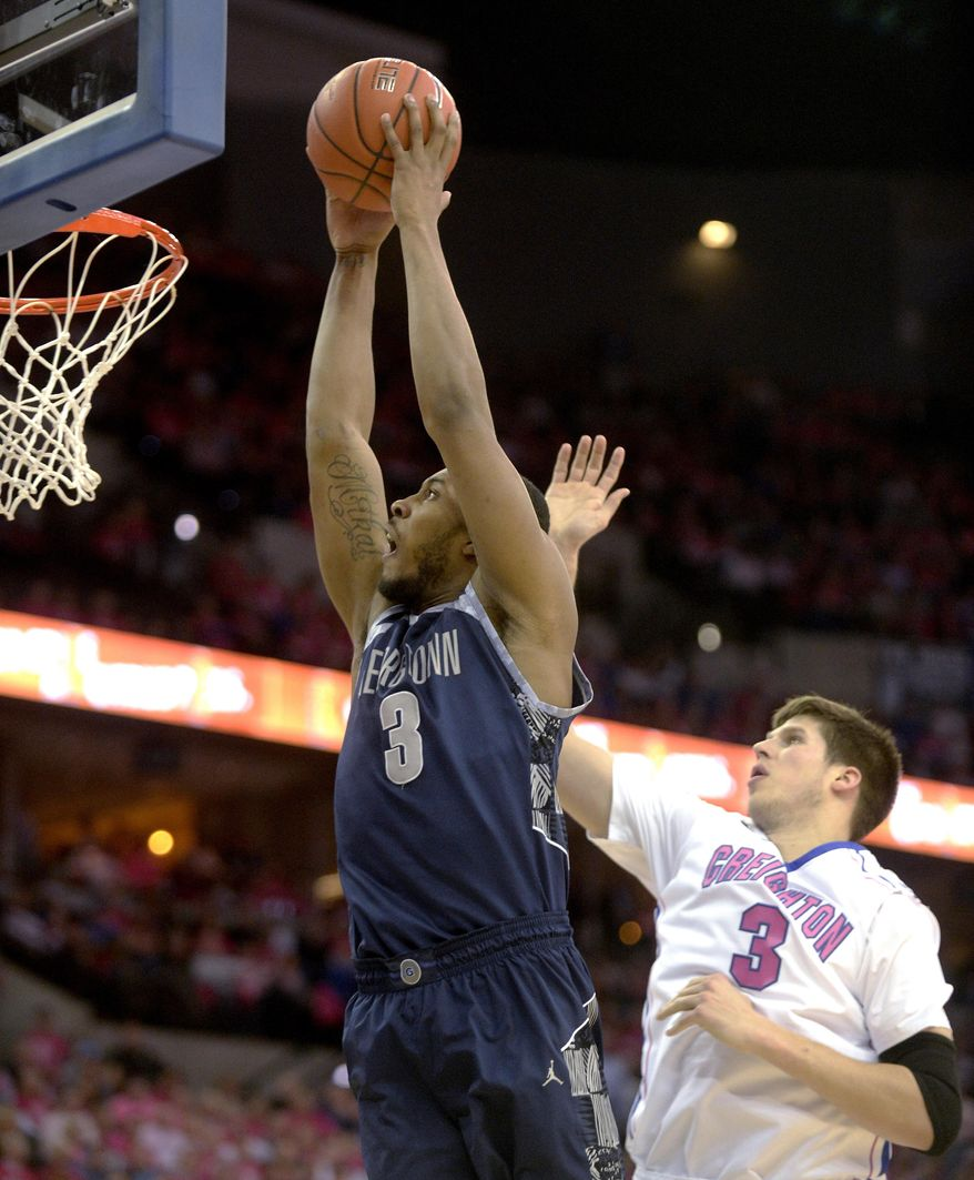Georgetown forward Mikael Hopkins (3) goes in for a dunk in front of Creighton's Doug McDermott (3) during the first half of an NCAA college basketball game in Omaha, Neb., on Saturday, Jan. 25, 2014. (AP Photo/Francis Gardler)