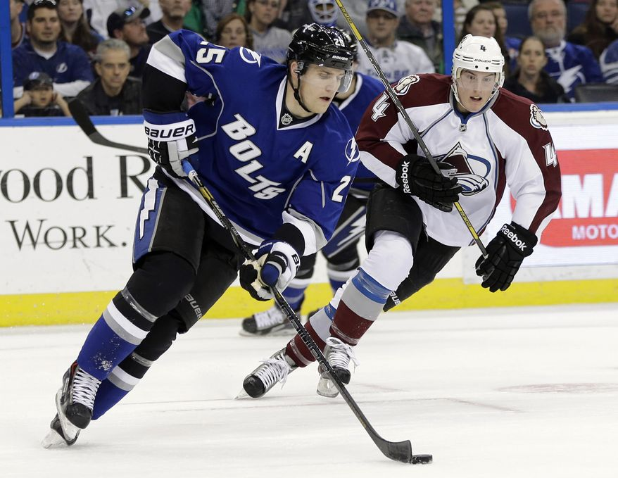 Tampa Bay Lightning defenseman Matt Carle (25) carries the puck past Colorado Avalanche defenseman Tyson Barrie (4) during the first period of an NHL hockey game Saturday, Jan. 25, 2014, in Tampa, Fla. (AP Photo/Chris O'Meara)