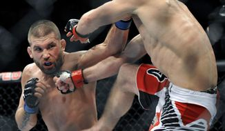 Jeremy Stephens left, fights Darren Elkins right, during the featherweight bout of an UFC mixed martial arts match in Chicago, Saturday, Jan., 25, 2014. (AP Photo/Paul Beaty)