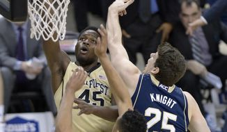 Wake Forest forward Arnaud William Adala Moto (45) gets by the Notre Dame forwards Tom Knight (25) and  Zach Auguste (30) during the first half of an NCAA college basketball game at the Joel Coliseum in Winston-Salem, N.C., Saturday, Jan. 25, 2014. (AP Photo/The Winston-Salem Journal, Bruce Chapman)