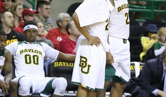 Baylor guard/forward Ish Wainright, center, along with forward Rico Gathers (2) and Royce O'Neale, left, watch from the bench in the second half of an NCAA college basketball game against Texas, Saturday, Jan. 25, 2014, in Waco, Texas. (AP Photo/Waco Tribune Herald, Rod Aydelotte)