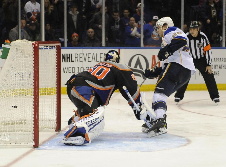 St. Louis Blues' Kevin Shattenkirk (22) shoots the puck past New York Islanders goalie Kevin Poulin (60) to score the winning goal during a shootout in an NHL hockey game on Saturday, Jan. 25, 2014, in Uniondale, N.Y. The Blues won 4-3. (AP Photo/Kathy Kmonicek)