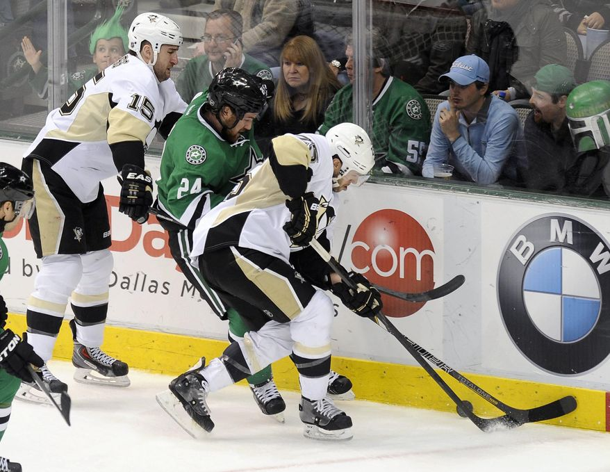 Dallas Stars defenseman Jordie Benn (24) fights for the puck along the boards with Pittsburgh Penguins left wing Tanner Glass (15) and center Andrew Ebbett in the first period during an NHL hockey game, Saturday, Jan. 25, 2014, in Dallas. (AP Photo/Matt Strasen)