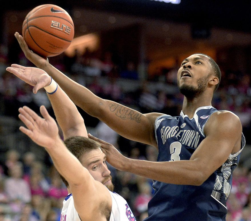 Georgetown forward Mikael Hopkins (3) gets fouled by Creighton forward Ethan Wragge as he drives to the basket during the first half of an NCAA college basketball game in Omaha, Neb., on Saturday, Jan. 25, 2014. (AP Photo/Francis Gardler)