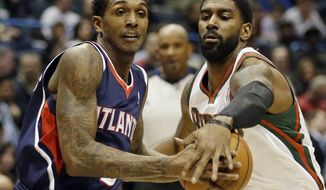 Atlanta Hawks' Louis Williams, left, drives against Milwaukee Bucks' O.J. Mayo during the first half of an NBA basketball game Saturday, Jan. 25, 2014, in Milwaukee. (AP Photo/Jeffrey Phelps)