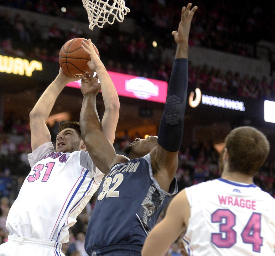 Creighton center Will Artino (31) and Georgetown center Moses Ayegba (32) compete for a rebound as the Creighton's Ethan Wragge looks on during the first half of an NCAA college basketball game in Omaha, Neb., on Saturday, Jan. 25, 2014. (AP Photo/Francis Gardler)