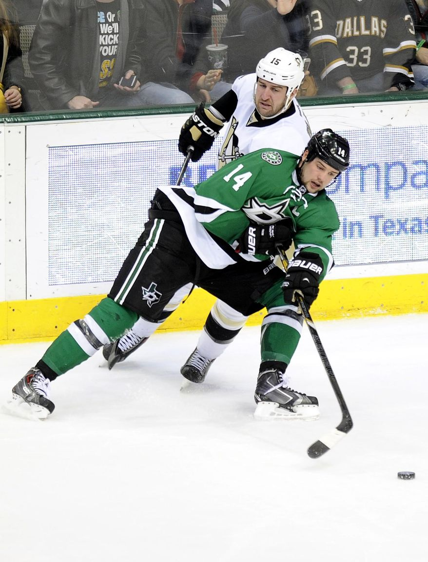 Dallas Stars left wing Jamie Benn (14) tries to control the puck in front of Pittsburgh Penguins left wing Tanner Glass (15) in the second period during an NHL hockey game, Saturday, Jan. 25, 2014, in Dallas. (AP Photo/Matt Strasen)