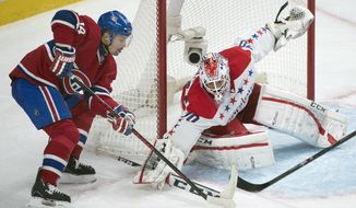 Washington Capitals goaltender Braden Holtby, right, makes a save against Montreal Canadiens' Tomas Plekanec during the third period of an NHL hockey game in Montreal, Saturday, Jan. 25, 2014. (AP Photo/The Canadian Press, Graham Hughes)