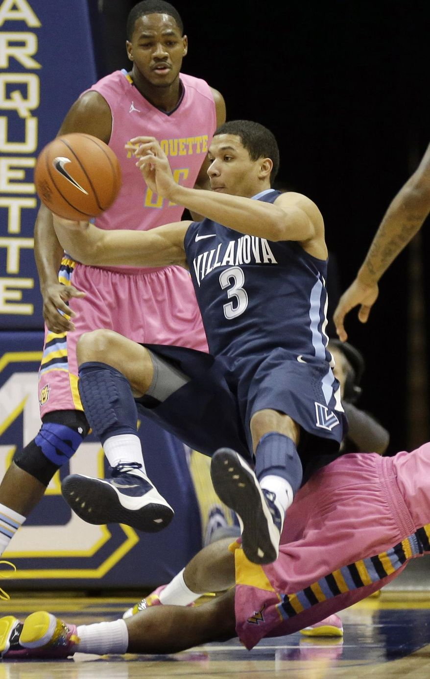 Villanova's Josh Hart(3) passes as he falls over a Marquette player during the first half of an NCAA college basketball game Saturday, Jan. 25, 2014, in Milwaukee. (AP Photo/Jeffrey Phelps)