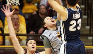 Nevada's Michael Perez puts a shot over Wyoming's Riley Grabau and Larry Nance, Jr., left, during an NCAA college basketball game Saturday, Jan. 25, 2014, at the Arena-Auditorium in Laramie, Wyo. Wyoming defeated Nevada 64-62 in overtime. (AP Photo/The Casper Star-Tribune, Alan Rogers)