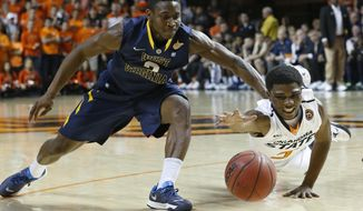 Oklahoma State guard Stevie Clark (5) dives for the ball in front of West Virginia guard Juwan Staten (3) in the first half of an NCAA college basketball game in Stillwater, Okla., Saturday, Jan. 25, 2014. (AP Photo/Sue Ogrocki)