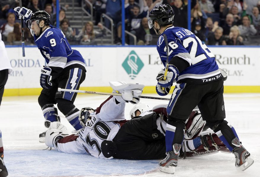 Tampa Bay Lightning center Tyler Johnson (9) celebrates after scoring past Colorado Avalanche goalie Sami Aittokallio (30), of Finland, during the second period of an NHL hockey game Saturday, Jan. 25, 2014, in Tampa, Fla. Looking on is Lightning's Martin St. Louis (26). (AP Photo/Chris O'Meara)