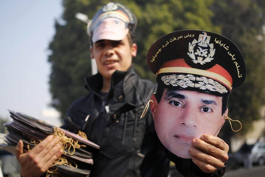 An Egyptian vendor displays a mask of Egypt's Defense Minister, Gen. Abdel-Fattah el-Sissi, in Tahrir Square, the epicenter of the 2011 uprising, in Cairo, Egypt, Saturday, Jan. 25, 2014. Egyptian riot police have fired tear gas to disperse hundreds of supporters of ousted Islamist President Mohammed Morsi protesting as the country marks the third anniversary of the 2011 uprising, as supporters of the military gathered in rival rallies in other parts of the capital, many of them urging military chief el-Sissi, the man who removed Morsi, to run for president.(AP Photo/Hassan Ammar)