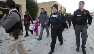 Law enforcement officers escort people from The Mall in Columbia, Saturday, Jan. 25, 2014, to a nearby parking lot following a shooting at the mall in Columbia, Md. Police say three people died at the mall including the presumed gunman.  (AP Photo/Manuel Balce Ceneta)