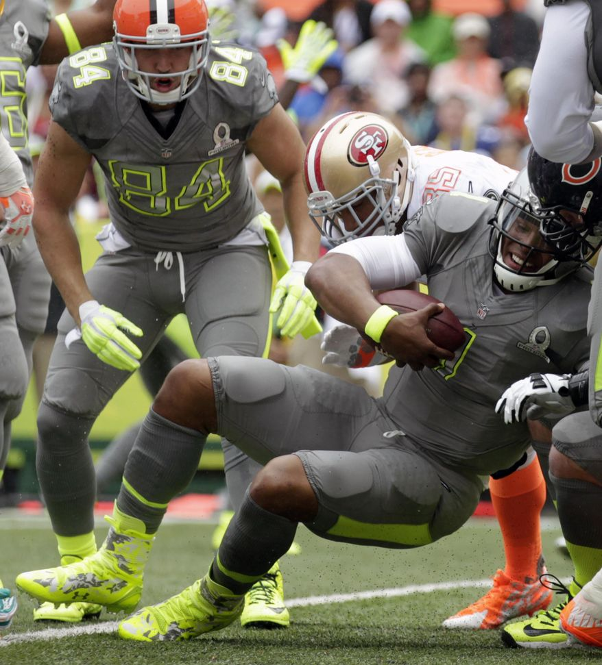 Carolina Panthers quarterback Cam Newton (1), of Team Sanders, pushes his way in for a touchdown in the second quarter quarter of the NFL Pro Bowl football game as Cleveland Browns tight end Jordan Cameron (84), of Team Sanders, looks on, Sunday, Jan. 26, 2014, in Honolulu. (AP Photo/Eugene Tanner)