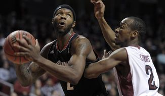 Cincinnati's Titus Rubles (2) drives past Temple's Will Cummings during the first half of an NCAA college basketball game on Sunday, Jan. 26, 2014, in Philadelphia. (AP Photo/Michael Perez)