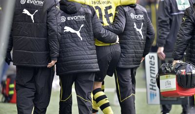 Dortmund's Jakub Blaszczykowski of Poland leaves the stadium injured during the German Bundesliga soccer match between Borussia Dortmund and FC Augsburg in Dortmund,  Germany, Saturday, Jan. 25, 2014. (AP Photo/Martin Meissner)