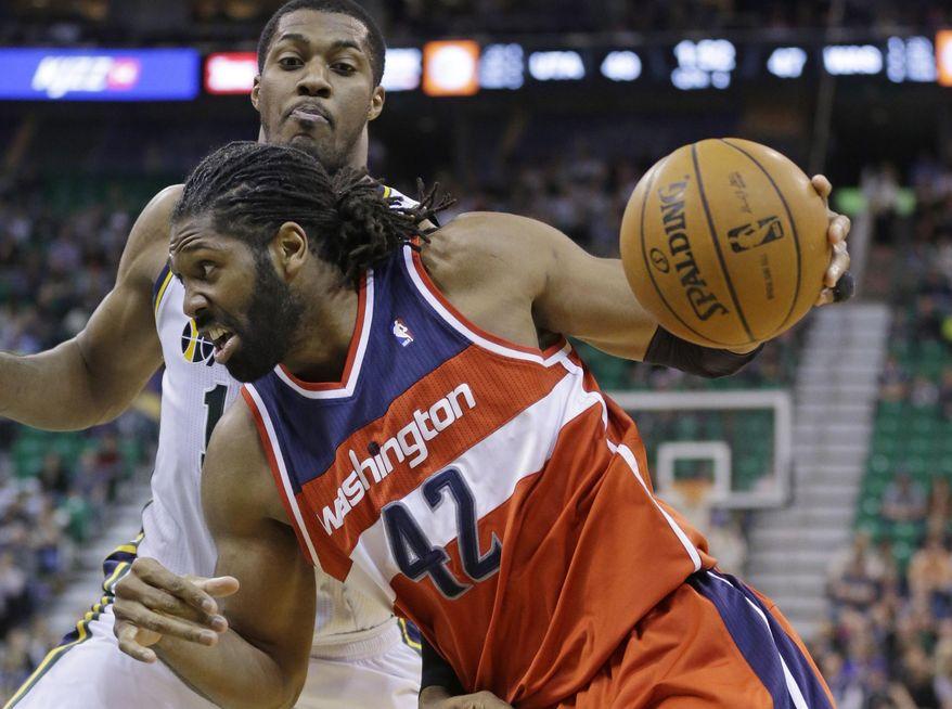 Washington Wizards' Nene (42) drives to the basket as Utah Jazz's Derrick Favors, rear, defends during the second quarter of an NBA basketball game Saturday, Jan. 25, 2014, in Salt Lake City. (AP Photo/Rick Bowmer)