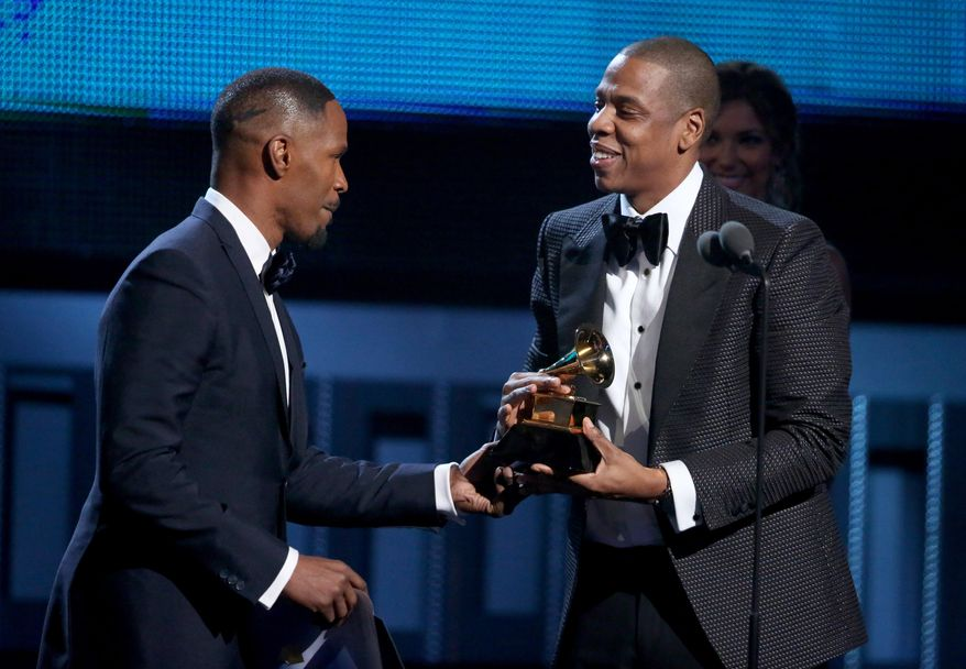 Jamie Foxx, left, presents Jay-Z with the award for best rap/sung collaboration at the 56th annual Grammy Awards at Staples Center on Sunday, Jan. 26, 2014, in Los Angeles. (Photo by Matt Sayles/Invision/AP)