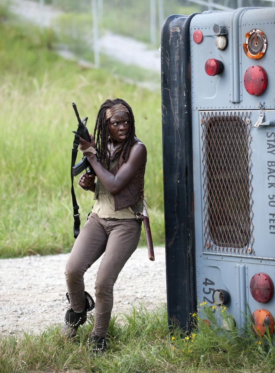 "FILE - This file publicity image released by AMC shows Danai Gurira as Michonne in a scene from the series ""The Walking Dead,"" which resumes episodes from its fourth season on Feb. 9. When she's not killing zombies on the rural Georgia set of The Walking Dead, Gurira is in Atlanta shopping for costumes for her own production or directing performances of it in Zimbabwe. (AP Photo/AMC, Gene Page)"