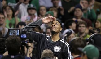 Brooklyn Nets forward Paul Pierce, center, formerly of the Boston Celtics, salutes the crowd during a tribute to him in the first half of an NBA basketball game against the Boston Celtics, Sunday, Jan. 26, 2014, in Boston. (AP Photo/Steven Senne)