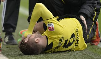 Dortmund's Jakub Blaszczykowski of Poland is injured on the ground and has to leaves the stadium during the German Bundesliga soccer match between Borussia Dortmund and FC Augsburg in Dortmund,  Germany, Saturday, Jan. 25, 2014. (AP Photo/Martin Meissner)