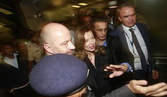 Valerie Trierweiler, center, former partner of French President Francois Hollande, is escorted by security after she arrived at the Chhatrapati Shivaji International Airport in Mumbai, India, Monday, Jan 27, 2014. Trierweiler is on a two-day visit to India.(AP Photo/Rafiq Maqbool)