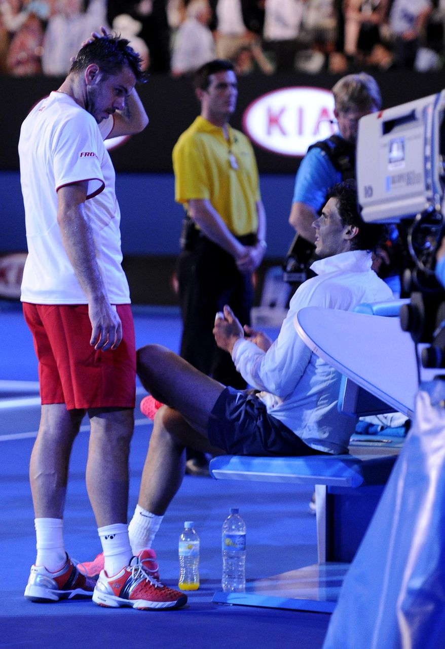 Stanislas Wawrinka of Switzerland, left, talks with Rafael Nadal of Spain before the trophy presentation, following his win in the men's singles final at the Australian Open tennis championship in Melbourne, Australia, Sunday, Jan. 26, 2014. (AP Photo/Andrew Brownbill)