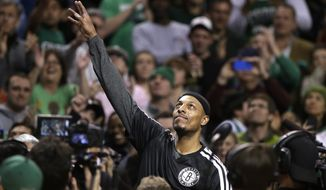 Brooklyn Nets forward Paul Pierce, center, formerly of the Boston Celtics, waves to the crowd during a tribute to him in an NBA basketball game against the Boston Celtics, Sunday, Jan. 26, 2014, in Boston. (AP Photo/Steven Senne)