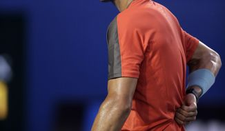 Rafael Nadal of Spain touches his back as he plays Stanislas Wawrinka of Switzerland during the men's singles final at the Australian Open tennis championship in Melbourne, Australia, Sunday, Jan. 26, 2014.(AP Photo/Rick Rycroft)