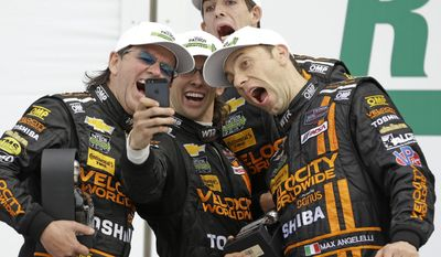 The Wayne Taylor Racing team, from left, Wayne Taylor, Jordan Taylor, Ricky Taylor and Max Angelelli, of Italy, take a group photo to celebrate their second place finish in the IMSA Series Rolex 24 hour auto race at Daytona International Speedway in Daytona Beach, Fla., Sunday, Jan. 26, 2014.(AP Photo/John Raoux)