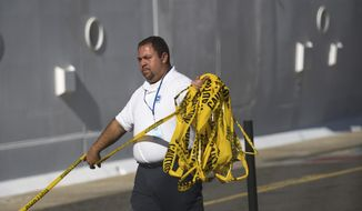 A West Indian Company employee removes a yellow caution barricade tape from around the Royal Caribbean International's Explorer of the Seas crusie ship, docked at Charlotte Amalie Harbor in St. Thomas, United States Virgin Islands, Sunday, Jan. 26, 2014. U.S. health officials have boarded the cruise ship to investigate an illness outbreak that has stricken at least 300 people with gastrointestinal symptoms including vomiting and diarrhea. (AP Photo/Thomas Layer)
