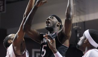 Cincinnati's Justin Jackson (5) shoots the ball over Temple's Devontae Watson, left, and Anthony Lee during the first half of an NCAA college basketball game on Sunday, Jan. 26, 2014, in Philadelphia. (AP Photo/Michael Perez)