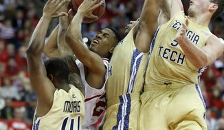 Georgia Tech's Jason Morris (14), Corey Heyward (30) and Daniel Miller, right, defend North Carolina State's Ralston Turner, second from left, as he shoots during the first half of an NCAA college basketball game at PNC Arena, Sunday, Jan. 26, 2014, in Raleigh, N.C. (AP Photo/The News & Observer, Ethan Hyman)