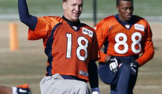 Denver Broncos quarterback Peyton Manning (18) stretches with wide receiver Demaryius Thomas (88) during NFL football practice at the team's training facility in Englewood, Colo., Saturday, Jan. 25, 2014. The Broncos are scheduled to play the Seattle Seahawks in Super Bowl XLVIII on Feb. 2. (AP Photo/Ed Andrieski)